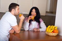 Couple drinking fresh orange juice in kitchen Stock Images