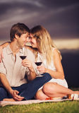 Couple drinking glass of wine on romantic sunset picnic Royalty Free Stock Photo