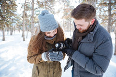 Couple drinking hot tea in winter park Royalty Free Stock Image