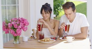 Couple drinking iced tea at breakfast outside. Young attractive couple drinking iced tea together at table with breakfast waffles  coffee  fruit and pink flower stock video
