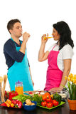 Couple drinking in kitchen. Couple drinkign fresh products in their kitchen and taking a break from cooking Royalty Free Stock Photos