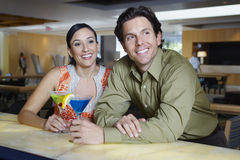 Couple Drinking Martinis At A Bar Royalty Free Stock Photos
