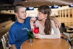 Couple drinking milk cocktail from one glass in bowling. Couple Royalty Free Stock Images