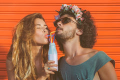 Couple drinking milk. Hipster couple drinking milk from bottle, going crazy and having great time together. Terracotta urban wall background Royalty Free Stock Photography