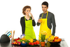 Couple drinking milk and orange juice. In their kitchen Royalty Free Stock Photography