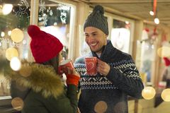 Couple drinking mulled wine at Christmas market. Young Couple Having Fun Outdoors At Christmas Time, Europe royalty free stock photo