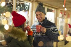Couple drinking mulled wine at Christmas market. Young Couple Having Fun Outdoors At Christmas Time, Europe stock photos