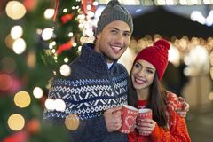 Couple drinking mulled wine at Christmas market. Young Couple Having Fun Outdoors At Christmas Time, Europe stock photography