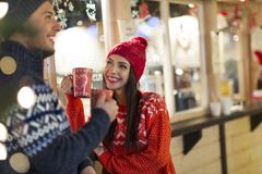 Couple drinking mulled wine at Christmas market. Young Couple Having Fun Outdoors At Christmas Time, Europe stock photo
