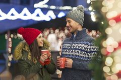Couple drinking mulled wine at Christmas market. Young Couple Having Fun Outdoors At Christmas Time, Europe stock image