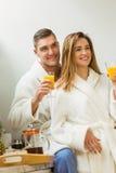 Couple drinking orange juice in bathrobes Royalty Free Stock Images