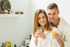 Couple drinking orange juice in bathrobes Royalty Free Stock Photography