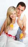 Couple drinking orange juice in bed Stock Image