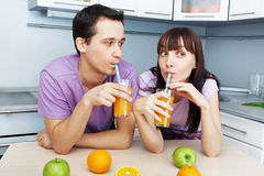 Couple drinking orange juice in the kitchen Royalty Free Stock Images