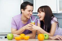 Couple drinking orange juice in the kitchen Royalty Free Stock Photo