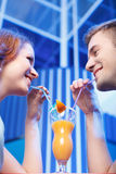 Couple drinking orange juice from same glass with straws. Stock Images