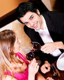 Couple drinking red wine clinking glasses. Young couple - man and woman - in a restaurant clinking the red wine glasses; focus on the glasses Royalty Free Stock Photography