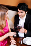 Couple drinking red wine clinking glasses. Young couple - man and woman - in a restaurant clinking the red wine glasses; focus on the glasses Royalty Free Stock Photo