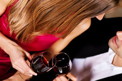 Couple drinking red wine clinking glasses. Young couple - man and woman - in a restaurant clinking the red wine glasses; focus on the glasses Stock Photo