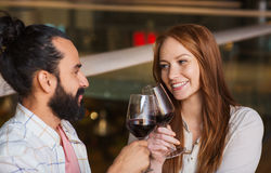 Couple drinking red wine and clinking glasses. Leisure, eating, food and drinks, people and holidays concept - smiling couple celebrating anniversary and Royalty Free Stock Photos