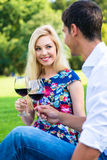 Couple drinking red wine on grass of park Royalty Free Stock Photography