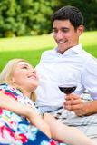 Couple drinking red wine on grass of park Stock Photo