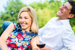 Couple drinking red wine on grass of park Royalty Free Stock Photos