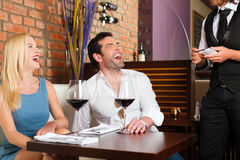 Couple drinking red wine in restaurant or bar. Attractive young couple drinking red wine in restaurant or bar, the waiter is taking the order Royalty Free Stock Photography