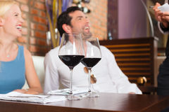 Couple drinking red wine in restaurant or bar. Attractive young couple drinking red wine in restaurant or bar, the waiter is taking the order Stock Photography