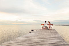 Couple drinking red wine at the seaside on a jetty. Woman and men couple drinking red wine at the seaside on a jetty Royalty Free Stock Images