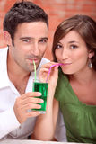 Couple drinking. The same cocktail Stock Photo