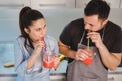 Couple drinking smoothie from the jar with a straw Stock Images