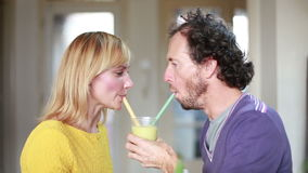 Couple drinking smoothie from same drinking glass stock video