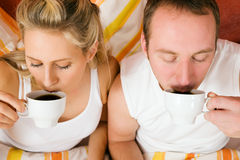 Couple drinking some coffee in the bead in morning Stock Image