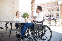 Couple drinking some coffee in a restaurant. Attractive young men on a wheelchair drinking some coffee in a restaurant with his girlfriend and having a good time Stock Image