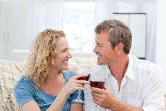 Couple drinking some red wine in the living room Stock Photo