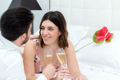Couple drinking sparkling wine on bed. Stock Image