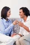 Couple drinking sparkling wine on the sofa Stock Photos