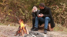 Couple drinking tea or coffee near fire. Couple in love talking and drinking tea or coffee near burning fire stock footage
