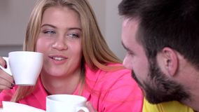 Couple drinking tea or coffee together at home, closeup. Happiness and healthy relationship concept, attractive couple drinking tea or coffee together at home stock video