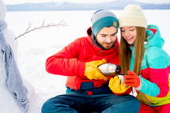 Couple drinking tea outdoors in winter Stock Photo