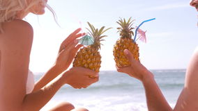 A couple is drinking their pineapple cocktail. On the beach stock footage