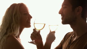 Couple drinking together with crossed arms against sunlight Royalty Free Stock Photo