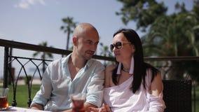 Man and woman drinking Turkish tea outdoors. Couple drinking Turkish tea at a table and talks stock footage