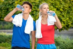 Couple drinking water after running Stock Photography