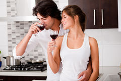 Couple drinking wine. Happy young couple drinking wine in kitchen stock photos