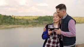 Couple drinking wine on banks of river, close-up. stock footage