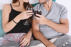 Couple drinking wine in bed. Stock Photography