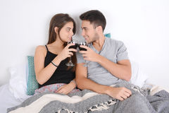 Couple drinking wine in bed. Stock Image