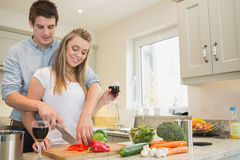 Couple drinking wine and cooking Stock Photos